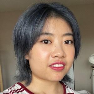 An Eastern Asian woman with short blue hair.