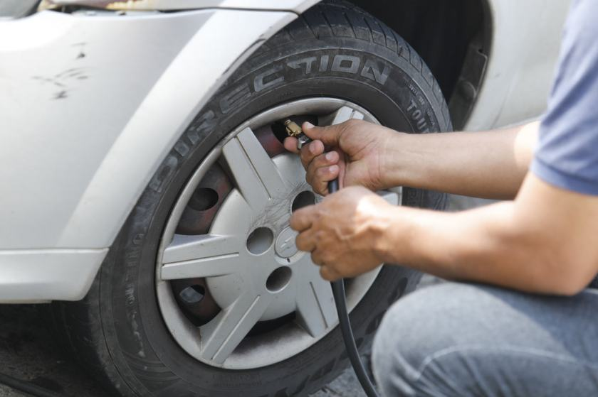 homem calibra pneu do seu carro