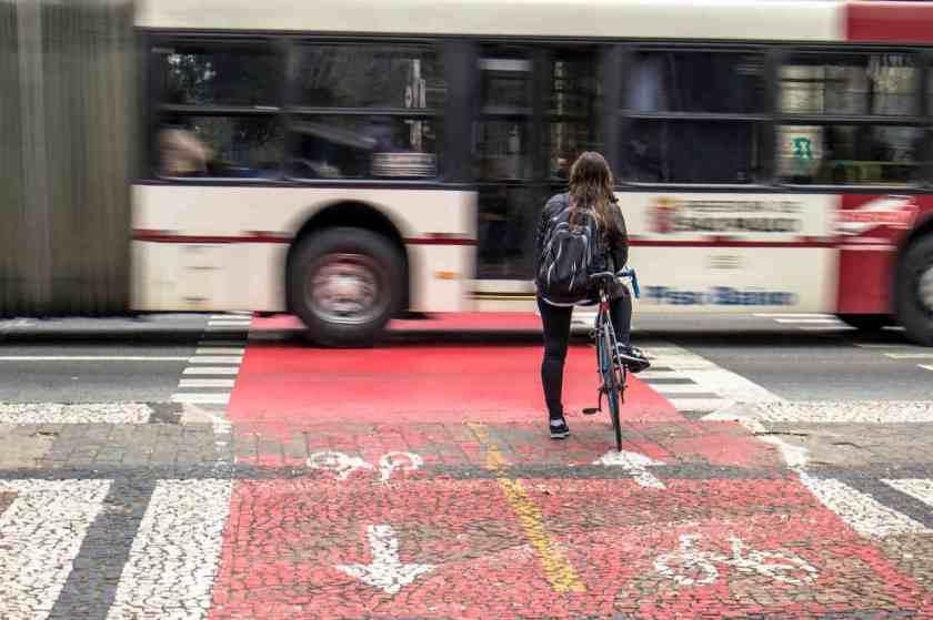 mulher ciclista em sao paulo na ciclovia espera passagem de onibus em avenida