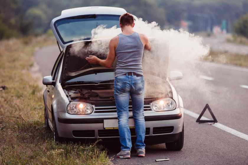 homem abre o capo do carro com muita fumaça saindo em rodovia