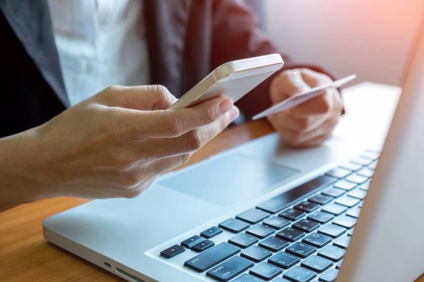 homem usa computador enquanto segura celular e documento