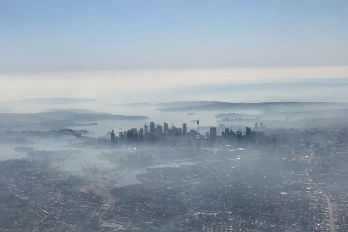 An image taken on a smart phone from a plane window shows smoke haze blanketing Sydney, Australia, November 19, 2019. AAP Image/Neil Bennett/via REUTERS    ATTENTION EDITORS - THIS IMAGE WAS PROVIDED BY A THIRD PARTY. NO RESALES. NO ARCHIVE.