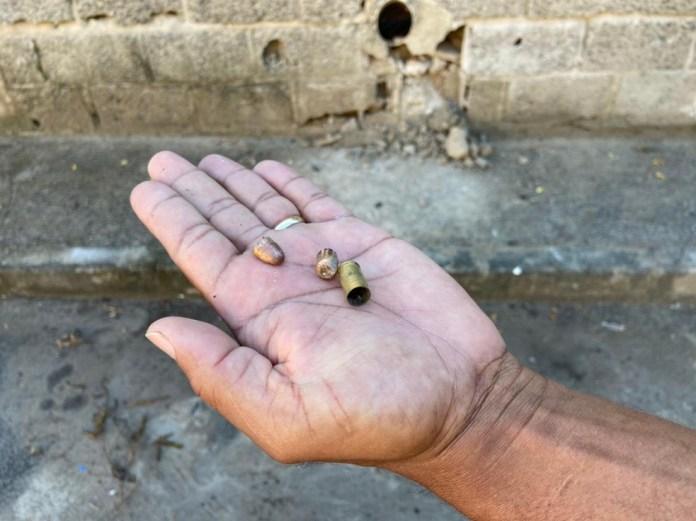 Morador mostra as capsulas de balas que ficaram na rua após dois homens serem assassinados em Vitória — Foto: Reprodução/Kaique Dias