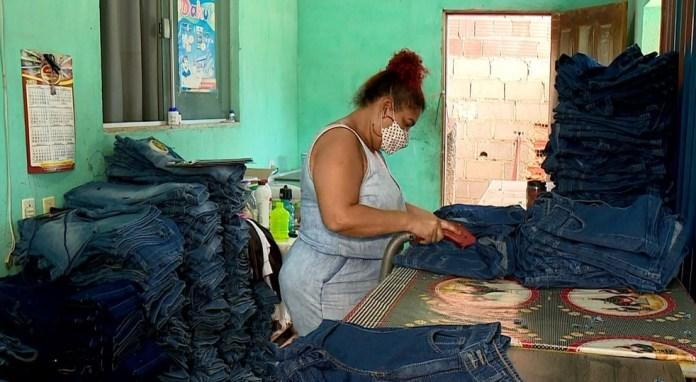 Mulher trabalha limpando linhas de peças de roupa