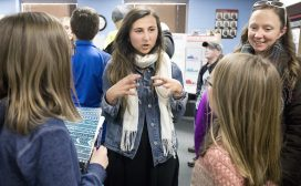 During the student expo at Columbine Elementary School, CC student Oliva Martinez '20 discusses findings with one of the students and parents.