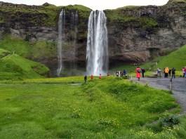 Seljalandfoss drops 200 feet over basalt flows and allows visitors to walk behind the falls.