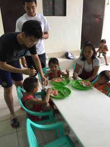 Joshua Tan and Javi Amador giving out vitamins to the kids.