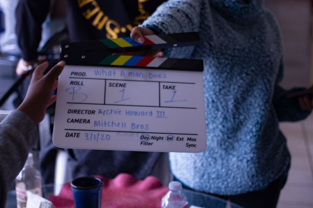 A clapboard. It says: Prod.: What A Man Does. Roll: B. Scene: 1. Take: 1. Director: Archie Howard III. Camera: Mitchell Bros. Date: 3/1/20. Day, Int