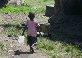 A child in the Mikingo Batwa Community carries a water jug. The Batwa struggle with access to healthcare after being evicted from their homes in the forest and being ostracized by the Kisoro community.