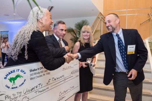 Chris Knight (right) received a surprise donation from Shake It Off for his Parkinson's research.
