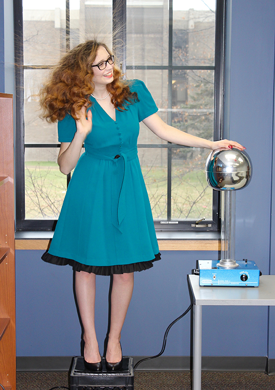 Danielle Maxwell touches an electrostatic generator.