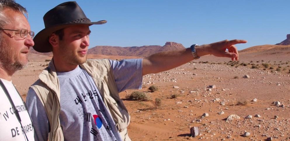 Nizar Ibrahim points out towards the horizon while exploring the Sahara Desert.