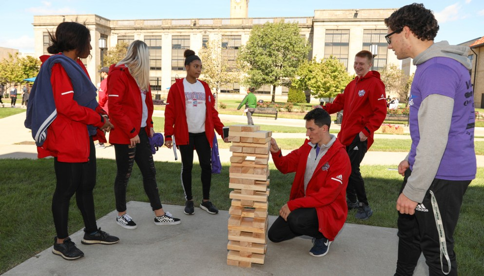 Group of student-athletes play giant Jenga at Homecoming 2018.