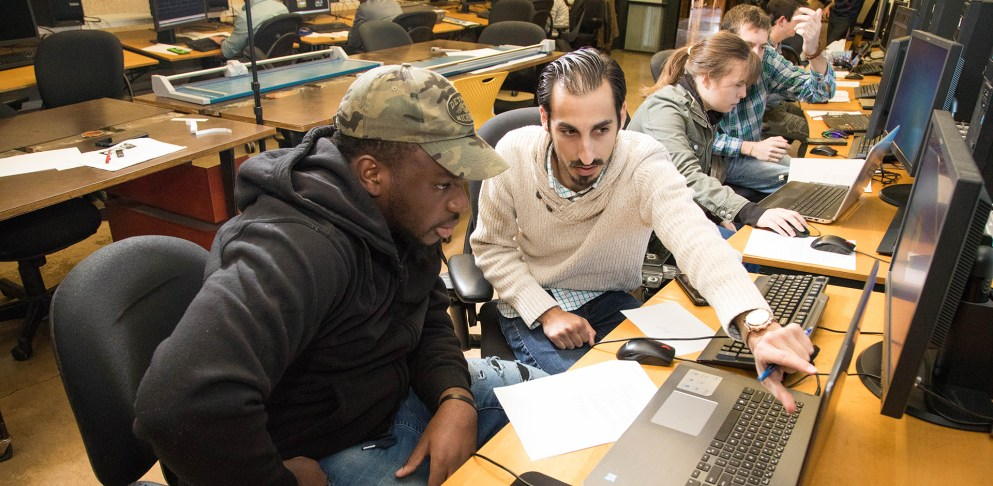 Architecture students collaborate on a studio project in the computer lab.