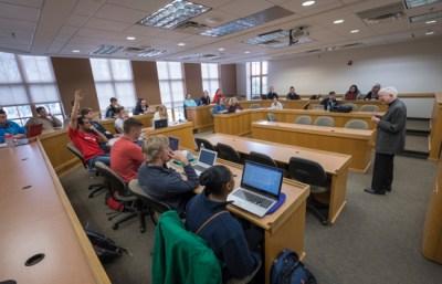 Fr. Cavanagh teaches a business class full of students.