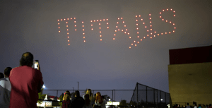 The word Titans is spelling out with drones as students watch the drone show.