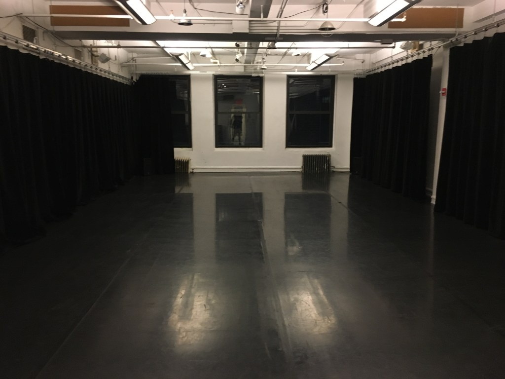 SITI's Zeisler Studio: a studio with a sprung floor, white walls with windows at its far end and black curtains along each wall.