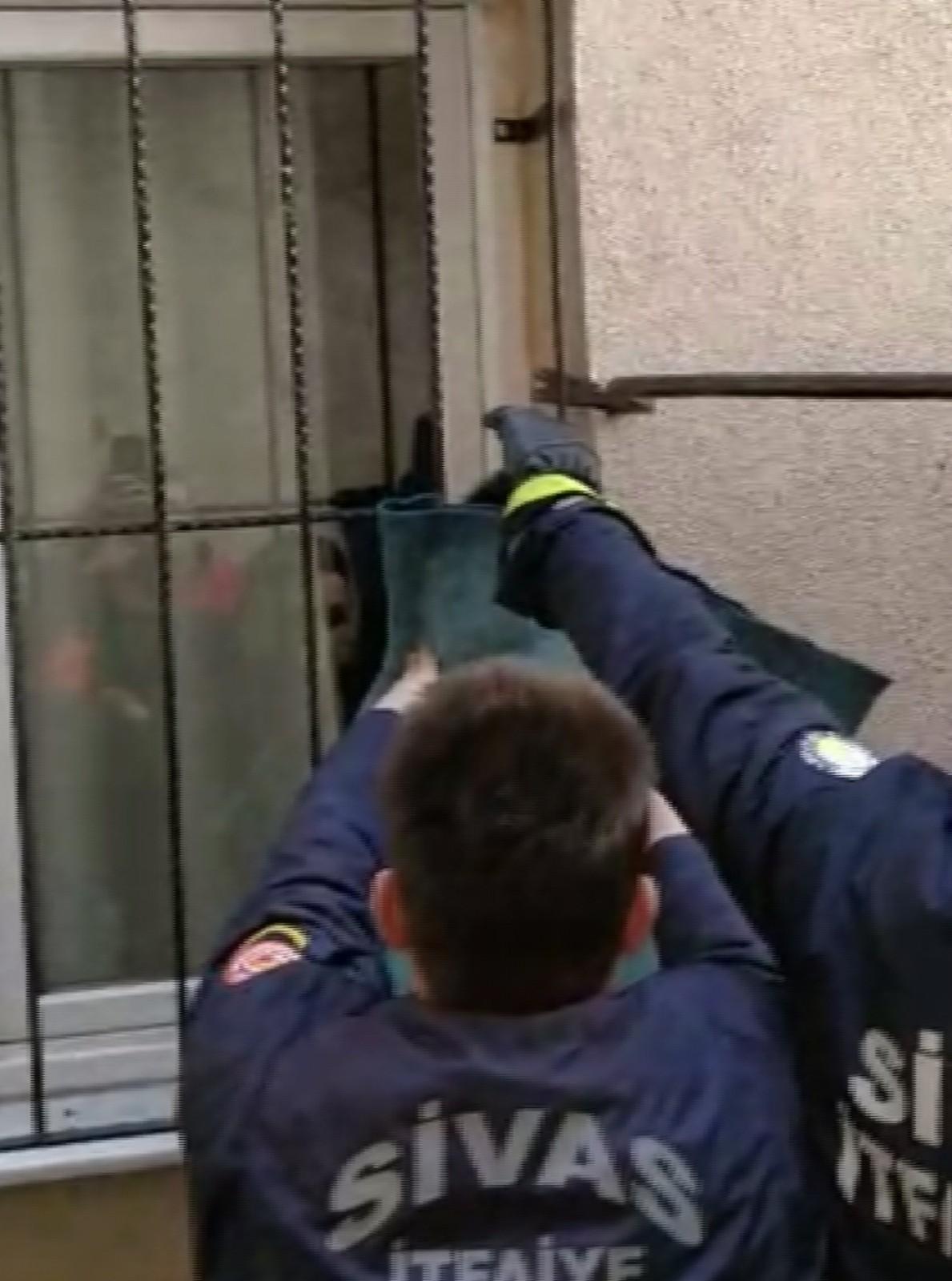 Pencere korkuluğunda asılı kalan kediyi itfaiye kurtardı