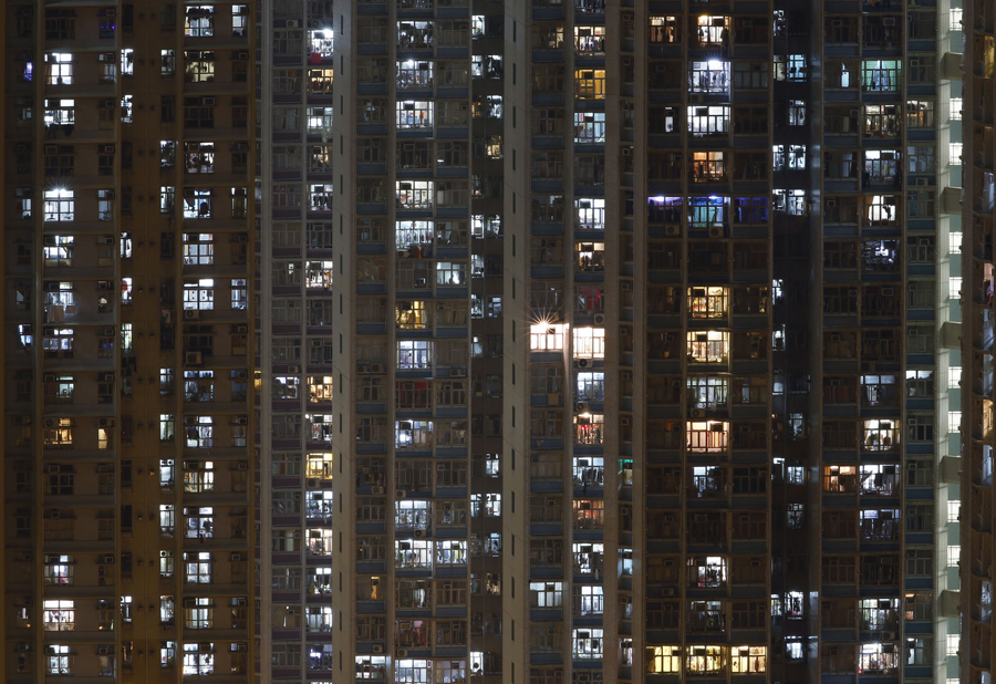 """In this Dec. 1, 2015 photo, an apartment building is seen in Hong Kong where both the living and the dead compete for space in the densely populated southern Chinese city. Limited land to build on and soaring property prices mean Hong Kong is fast running out of space to store the dead. That's a problem for residents who visit grave sites on """"tomb sweeping"""" holidays to burn incense and pay respects to venerated dead ancestors as prescribed by Chinese tradition. (AP Photo/Kin Cheung)"""