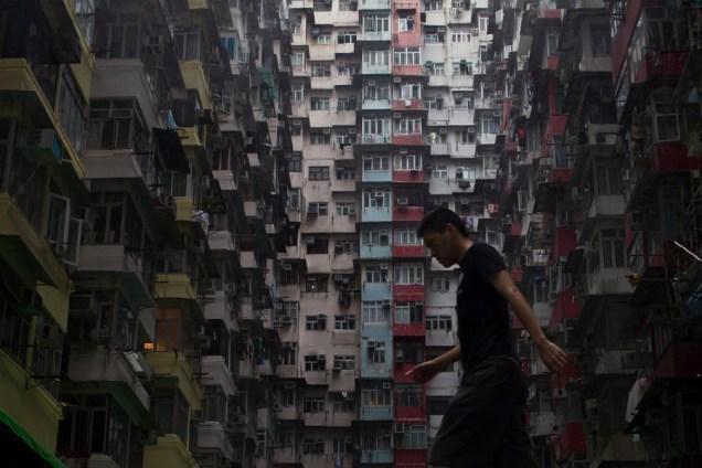 A man walks before a residential apartments in Hong Kong on May 16, 2015. AFP PHOTO / DALE DE LA REY (Photo credit should read DALE de la REY/AFP/Getty Images)