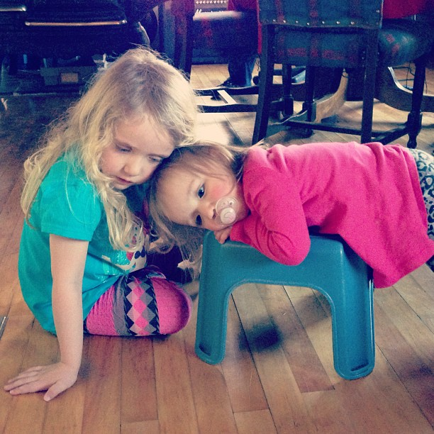 Subversive snuggling... Ellie is trying to get the stool back from Gwen by being overly nice.