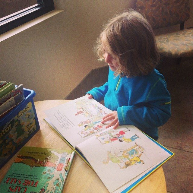 Reading by herself.