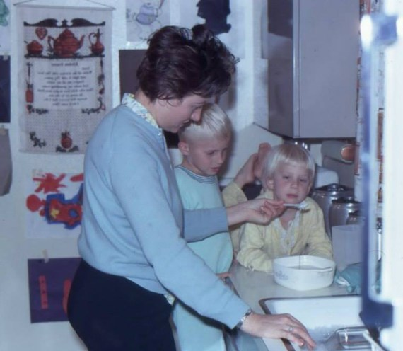 My grandmother cooking something delicious while my uncle and mother watch.