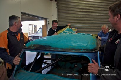 Removing the vinyl roof - you can see the Cooper's original colour. From left to right: Chris Jones (M.I.N.I.); Garry Grant (Alltrax NZ); Dave Pinker (M.I.N.I.); Garry Orton (VictoryR). Photo by Mike Wilson ©2011. All Rights Reserved.