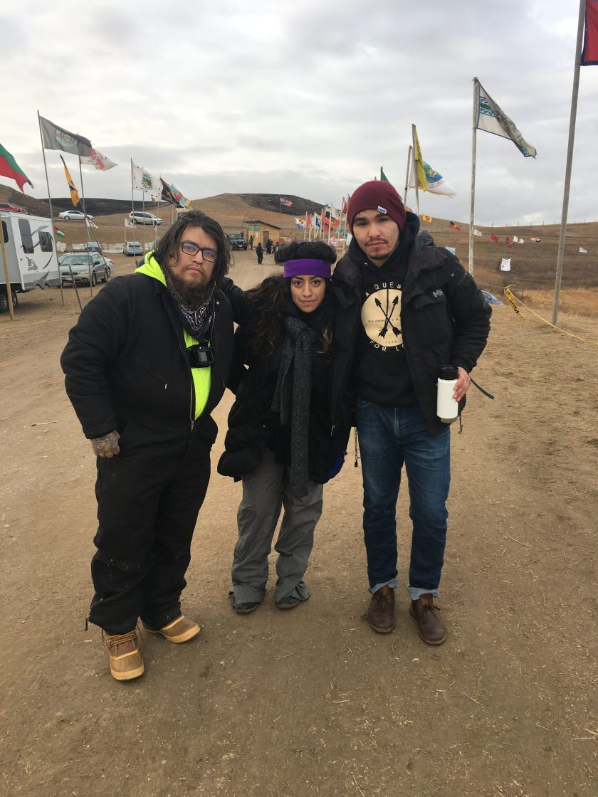 Natalie with childhood friends standing along the road with all nations flags in the background, Photo credit: Analu M. Lopez