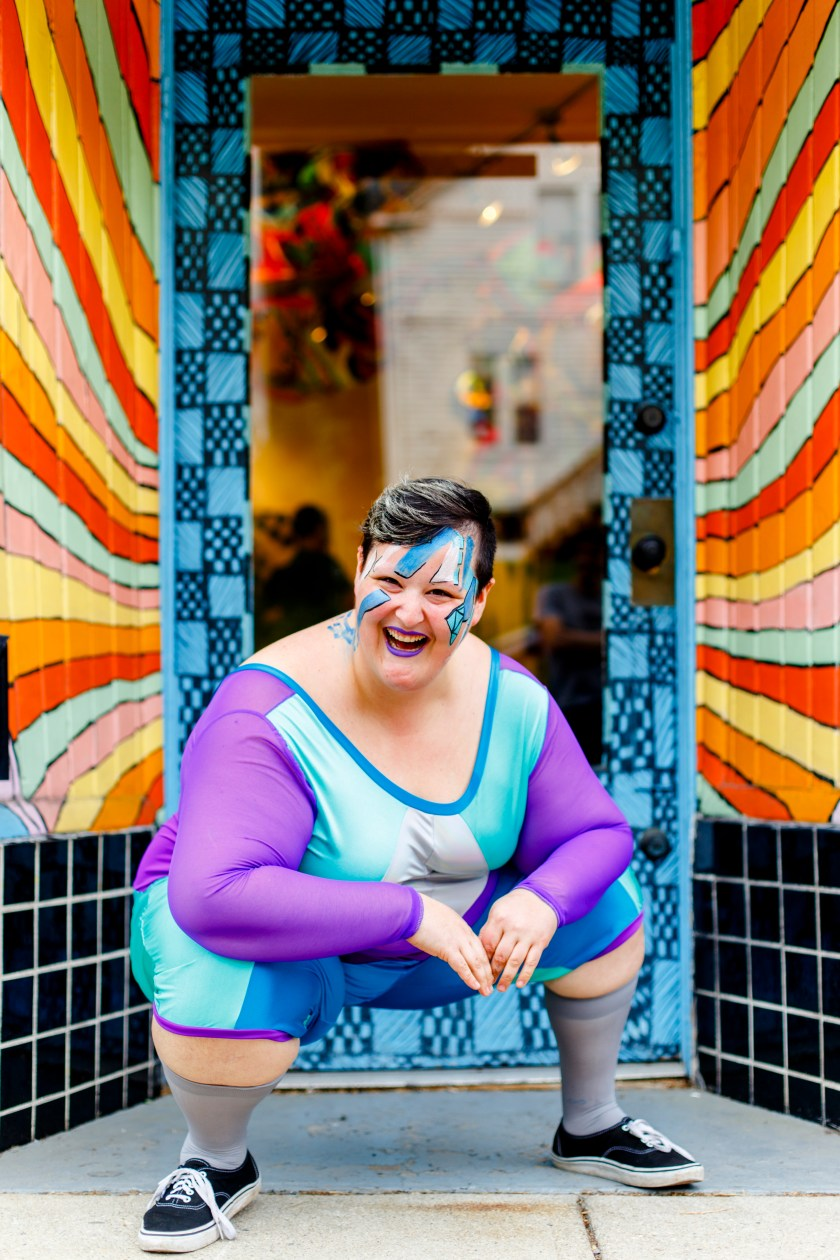 Sea Sprang squats down as they laugh in front of a doorway wearing a purple and blue geometric patterned piece with high socks and black sneakers. Photo credit Grace DuVal.