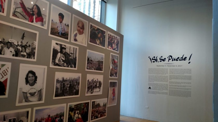 Photo of two walls showing several portraits and events from the UFW and wall text for the show ¡Sí, Se Puede!