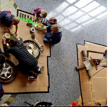 An image of for people working on the ground on flattened boxes. They are surrounded by miscellaneous items such as tires, a fan, and bright green tape.