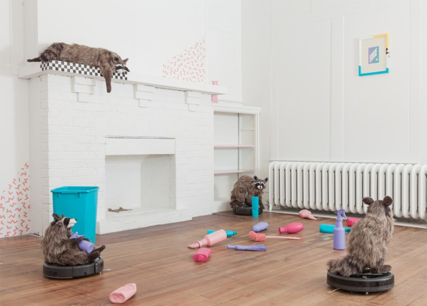 "Three homemade raccoons balanced on top of Roombas in a room scattered with multicolored bottles of cleaning products. In the background, a fourth raccoon is balanced on top of a white fireplace, and seems to look down on the scene. Lux, Maria. ""Dominus."" 2017. installation view. ""Dominus,"" DEMO Project, Springfield, IL. Courtesy of artist. Photos: Will Arnold."