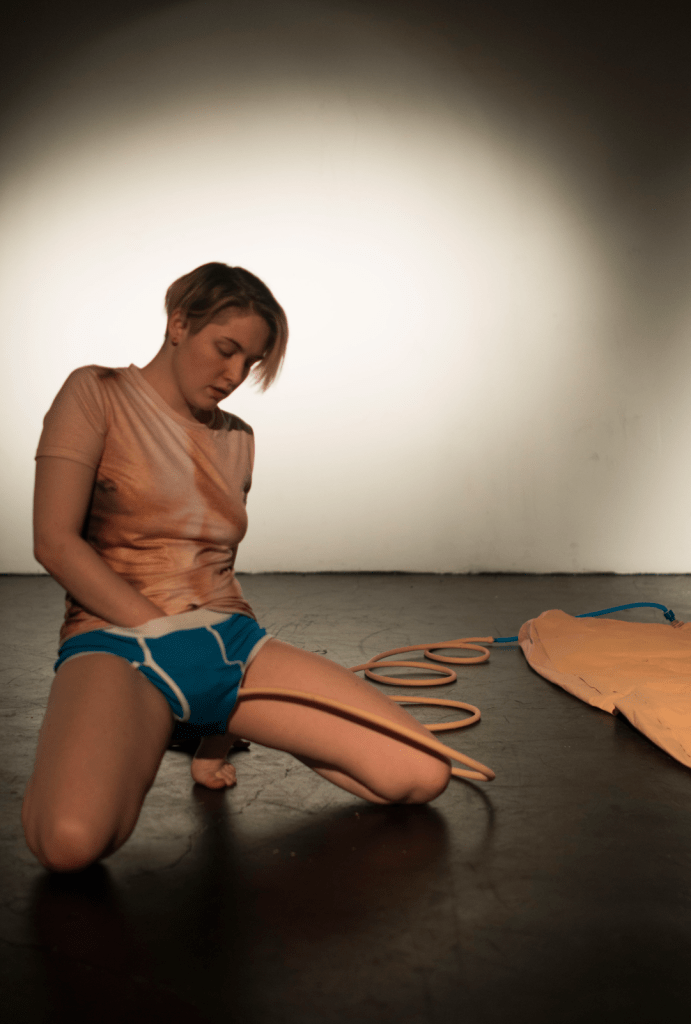 The artist is kneeling on the floor with one hand down their blue underwear. A hose connected to an air mattress is on the right side of the photo. Photo by C.V Peterson