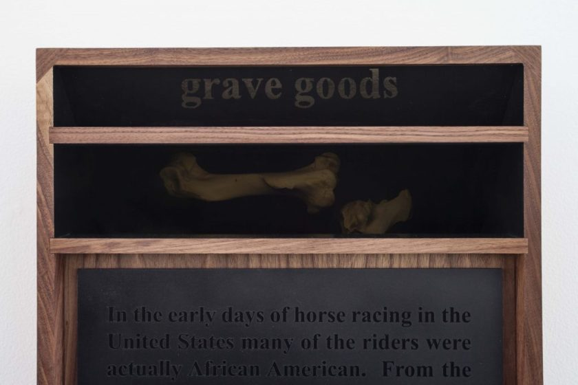 """Three stacked horizontal panels, black and framed with brown wood; with text at the top reading """"Grave Goods"""". Under that is a panel with an image of two horse bones, then finally a large panel with a long paragraph of text in black on a black background."""