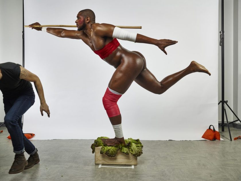 Courtesy of the artist. A figure is posed in the middle of the frame, with no clothing, but two red pieces of material around the stomach and calf. They are balancing on a wooden box. The background is white. A figure is seen running out of the frame on the left hand side.