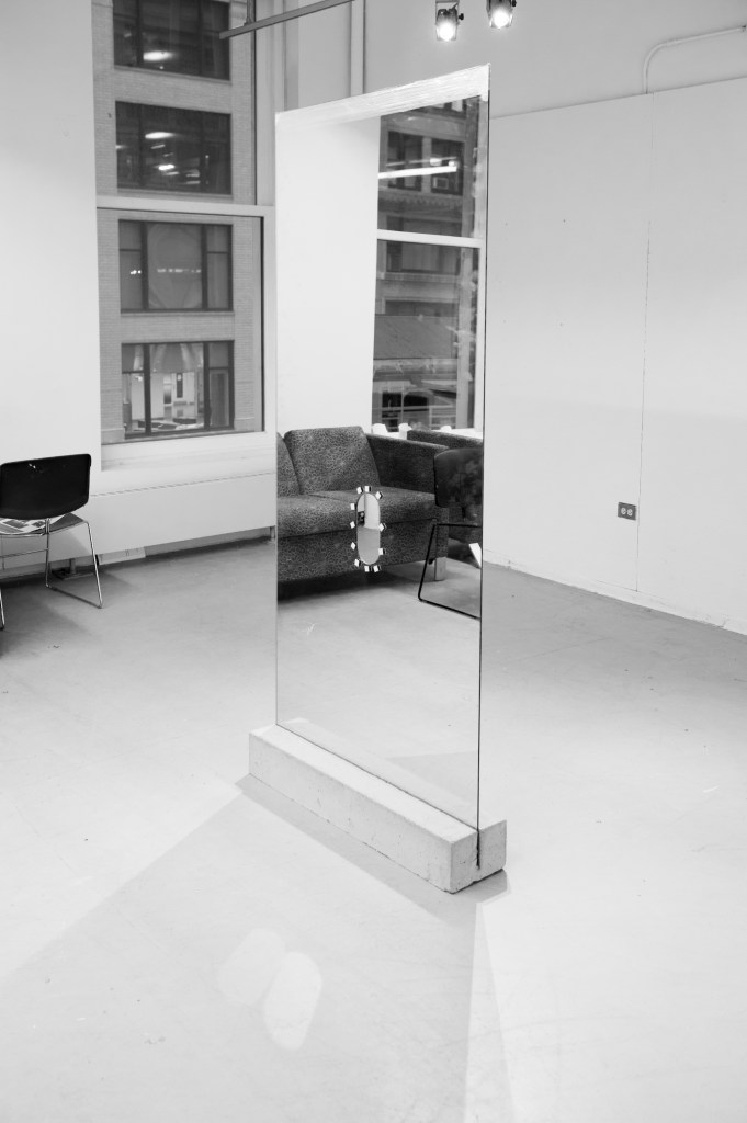Courtesy of the artist. A long, tall mirror sits in the middle of a gallery space with a hole through the center.