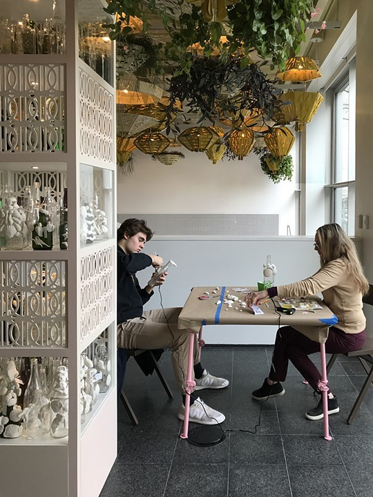 "The image shows two people sitting at a table covered in shells and other miscellaneous craft supplies. They are decorating empty liquor bottles by gluing on shells. Next to the table is a shelf structure with empty liquor bottles as part of ""Open 24 Hours."" The activity pictured is part of the workshop series that accompanies Soto's installation at the MCA. Image courtesy of the artist."