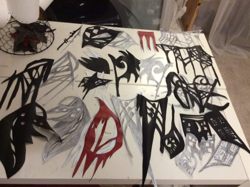 Image of Denenge's studio with elaborately cut pieces of black, red, and white paper part of work in progress. Image courtesy of D. Denenge Duyst-Akpem.