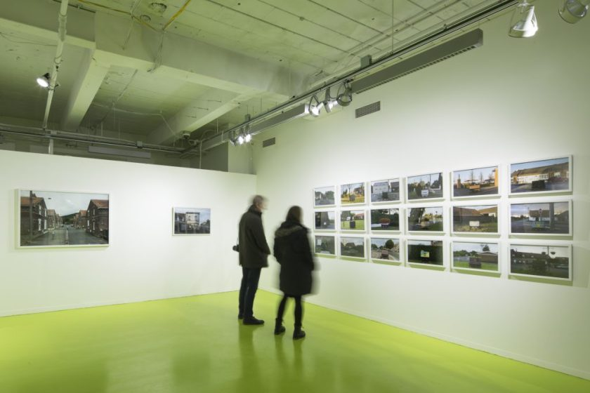 "Two viewers take in David Schalliol's ""Mining Basin (Hauts-de-France)"". To their left are two isolated photographs of the town; on the wall in front of them is a series of images of the region's homes and distinctive coal carts, arranged in a grid that takes up most of the wall. Photo courtesy of Hyde Park Art Center."