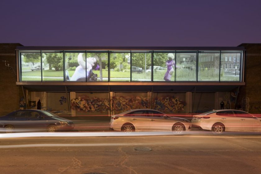 "Justine Pluvinage's ""Amazons"" as seen from Cornell Ave outside the Hyde Park Art Center. A 10-panel display showing a grassy urban environment and a young woman is projected onto the building's facade. Photographer:"
