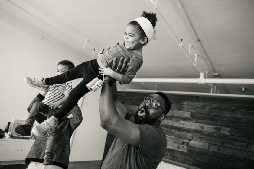 A black-and-white photograph of the artist, his wife, and their twin toddlers at play. They are in a spacious room with high ceilings. In the foreground, the artist lifts his daughter above his head and she laughs. In the background, his wife Katie lifts their son to her shoulder. Photo by Becca Heuer Photography.