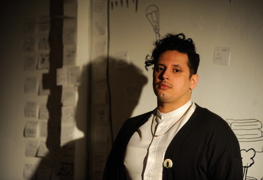 Ricardo Gamboa, host of the Hoodoisie, poses right before the start of February 3rd's episode at the Chicago Art Department. Gamboa wears a white button-up shirt, gold chain, and black sweater with a Hoodoisie pin. Their shadow is case on the white wall behind them. Photo by William Camargo