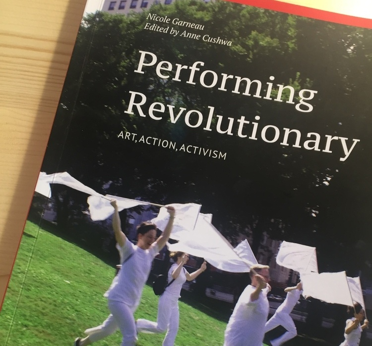 """Image shows the cover of the book """"Performing Revolutionary: Art, Action, Activism."""" The cover shows several people wearing white waving white flags while running down a hill. in Grant Park."""
