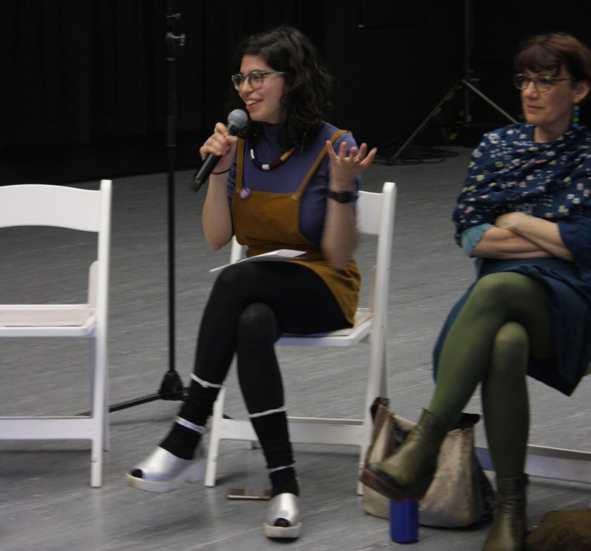 The co-founder smiles and holds a microphone, her other hand raised in expression as she talks. She sits with her legs crossed, a piece of paper folded on her lap. To the speaker's left, a discussant sits with arms folded and legs crossed. To the speaker's right is an empty chair.
