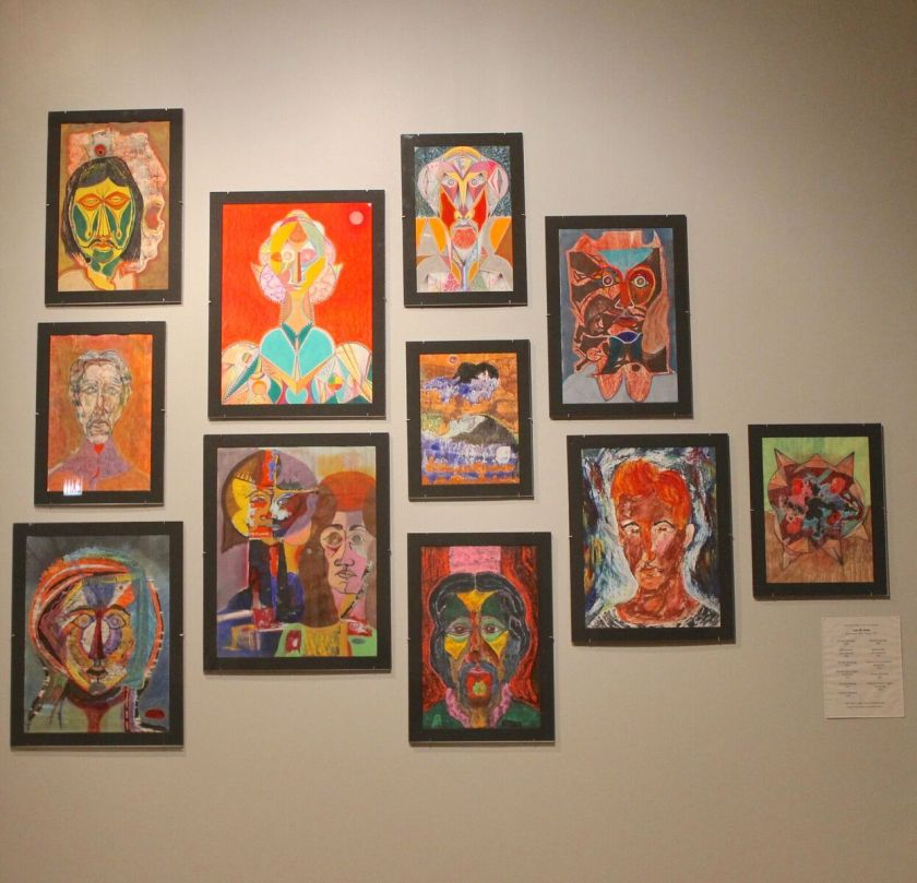 Detail of an exhibition wall showing portraits by Luis M. Ortiz. Eleven portraits are displayed. The portraits use flattened or angular planes for the faces and features, in alternating bright and earthy colors. In some places the paint on the portraits is rough and textured. Photo by Melissa Patiño Cervantes.