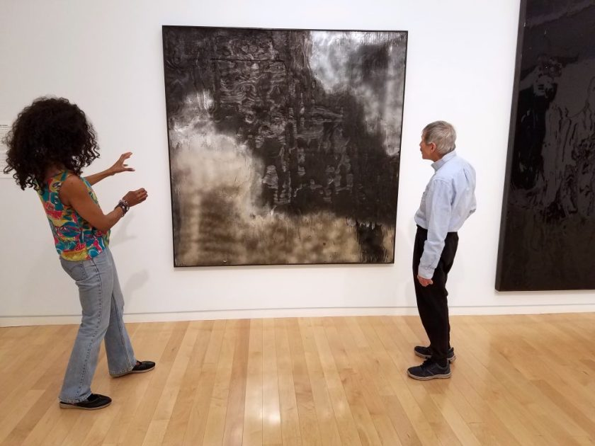 The poets stand in a gallery with an artwork between them—Lorraine with both hands up gesturing toward it and David looking at it, both with their backsides to the camera. The artwork is a large-scale, square piece, hanging on the wall. It is two-dimensional, with a textured black section stretching roughly diagonally from top-left to bottom-right corner, and with reflective silver sections in the top-right corner and along the bottom and in the bottom-left corner.