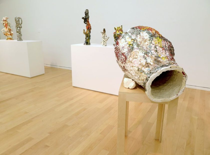 """This photo shows part of the gallery. In the foreground on the right-hand side of the image, """"Goya Dreaming"""" sits on a narrow wood table. The artwork is oblong in shape, with a colorful, textured surface, and a small whitish piece touching its side. From this angle, a large opening is visible. In the background are two broad pedestals (partially seen) displaying several sculptural objects."""