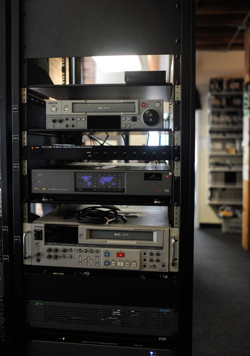 The image shows various equipment used for digitizing and playing different video formats. In the background, shelves hold video from Media Burn's collection. Photo by William Camargo.