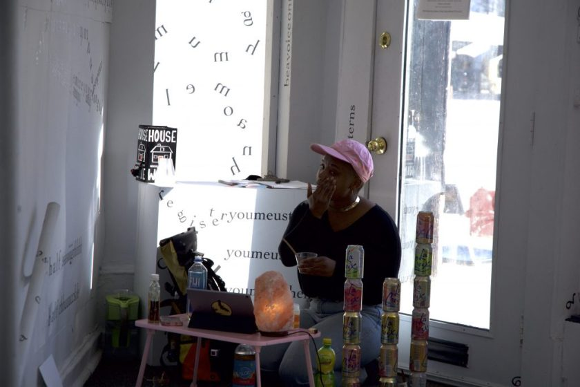 This is a still image of a performance. The performer sits inside the front door to the gallery, next to a wall covered in black vinyl letters and words. The performer wears a light pink baseball cap and sits behind a small, light pink table with a small, light pink, Himalayan salt lamp on it. Other objects near the performer include bottles of water and other liquids; towers of stacked, pastel LaCroix cans; and a cell phone and a tablet. The performer holds a small cup with one hand and spreads something on a cheek with the other.